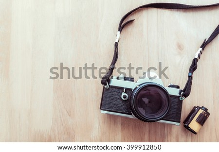 Vintage camera and a photo film in cartridge on wooden background - stock photo