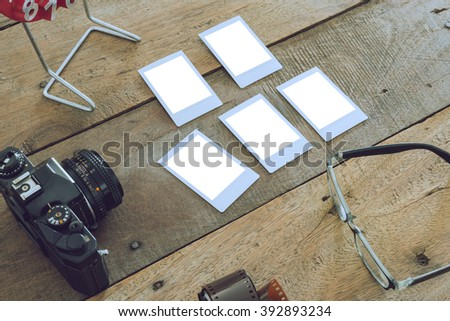 Vintage camera and blank old photograph on wooden background - stock photo