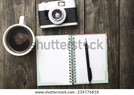 Vintage camera, diary with pan and cup pf coffee on wooden table.  - stock photo