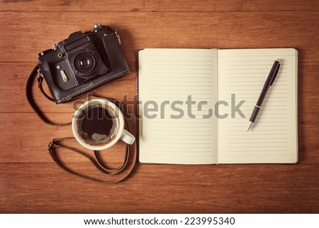 Vintage camera, diary with pan and cup pf coffee on wooden table. Instagram style toned photo. - stock photo