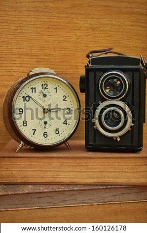 Vintage camera on book and clock  - stock photo