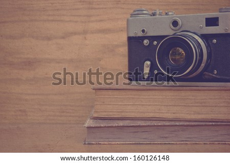 Vintage camera on book on wooden background - stock photo