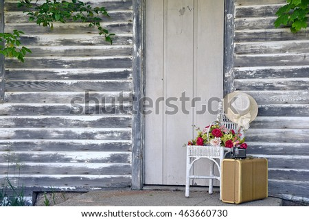 vintage camera on old suitcase with flowers on white wicker chair by rustic door
