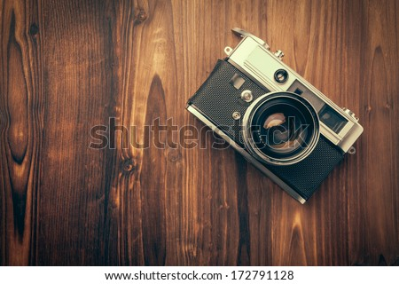 Vintage camera on wooden background - stock photo