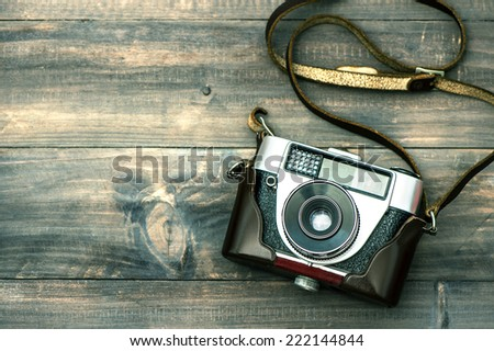 Vintage camera on wooden background. Top view. Retro style toned picture - stock photo