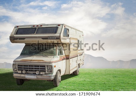 vintage camper at meadow under a blue sky - stock photo