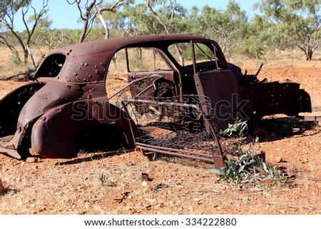 Vintage car abandoned in bush land.Rusty cars with bullet holes in outback.Old car - stock photo
