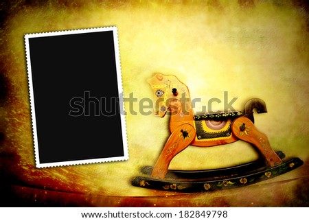 vintage card, old rocking horse and photo frame - stock photo