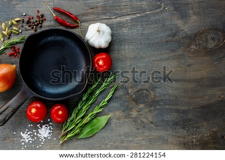 Vintage cast iron skillet and ingredients for cooking on dark wooden board. Food background with copyspace. - stock photo