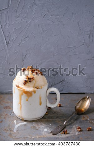 Vintage ceramic cup with homemade caramel and Hazelnut butter Ice cream, served with caramel syrup and crispy nuts over rusty metal textured background. - stock photo