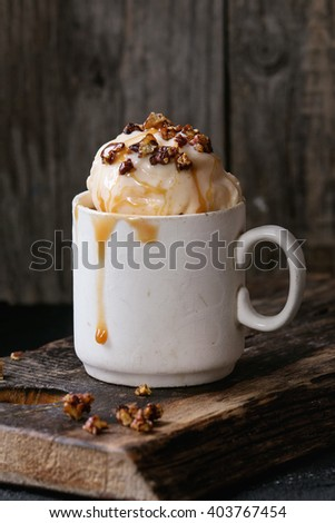 Vintage ceramic cup with homemade caramel and Hazelnut butter Ice cream, served with caramel syrup and crispy nuts on old wooden chopping board over black textured background. - stock photo
