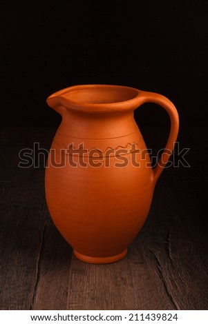Vintage ceramic pot on wooden table in dark background (Still life) - stock photo