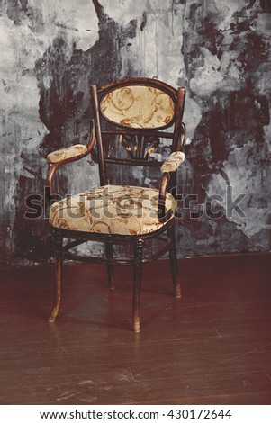 Vintage chair on the background of shabby wall.  Oldshool 70s colour graded.