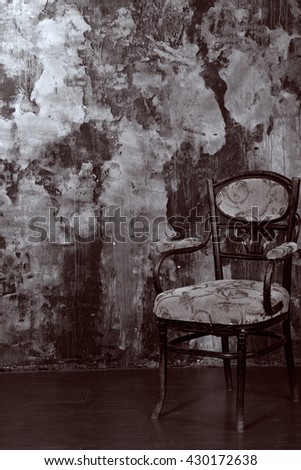 Vintage chair on the background of shabby wall. Vintage Black and White colour graded.