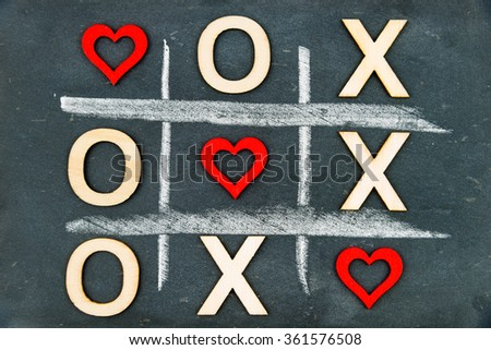 Vintage chalkboard with Tic Tac Toe Game Competition XO Win created of wood letters and red hearts, letters O and X replaced with red heart shapes, Challenge and Love Always Wins Concept  - stock photo