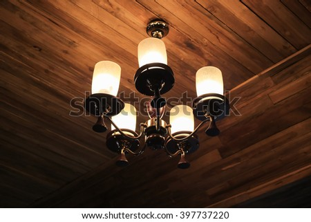 Vintage chandelier hanging on ceiling wooden. - stock photo