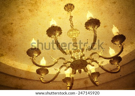 Vintage chandelier hanging under a ceiling in home - stock photo