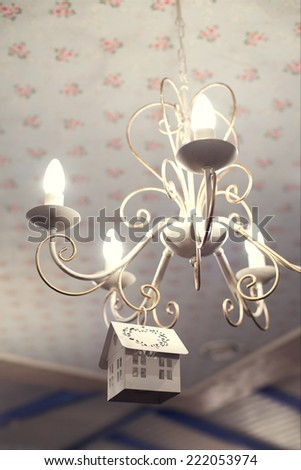 Vintage chandelier with small wooden decorative house on it - stock photo
