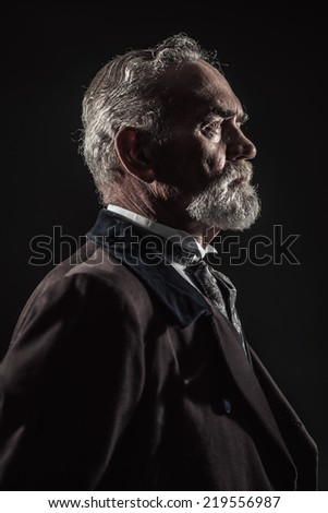 Vintage characteristic senior man with gray hair and beard. Studio shot against dark background.