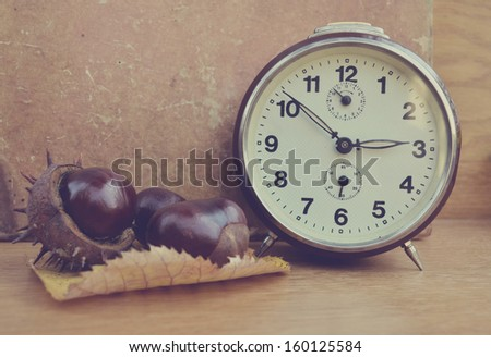 Vintage chestnut and clock on wooden background - stock photo
