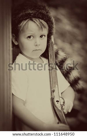 Vintage child with toy rifle and coon skin cap - stock photo