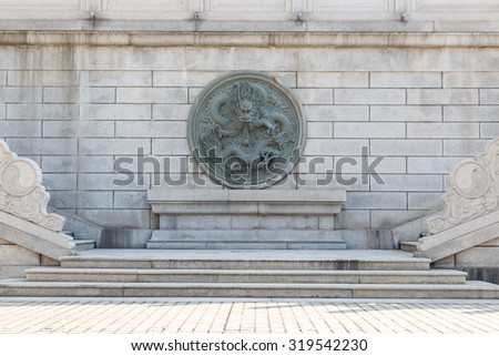 Vintage Chinese stone dragon statue on wall and stairs - stock photo
