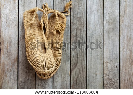 Vintage Chinese straw shoes on wooden wall - stock photo