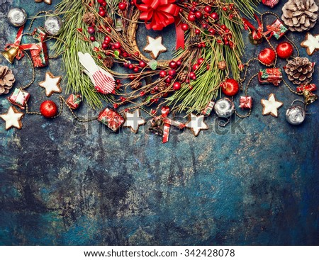 Vintage Christmas background with red decoration,  wreath of red winter berries and cookies, top view, horizontal border - stock photo