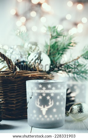 Vintage Christmas decor, old Christmas decorations in a basket, lanterns, garlands and spruce branches on a white table.
