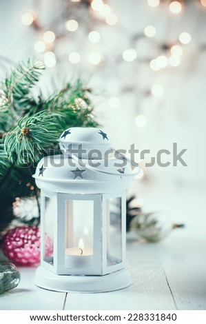 Vintage Christmas decor, old Christmas decorations, lanterns, garlands and spruce branches on a white table. - stock photo