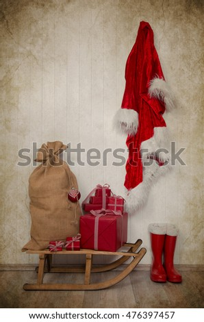 Vintage christmas decoration in red and white colors with old sledge and presents on wooden background.