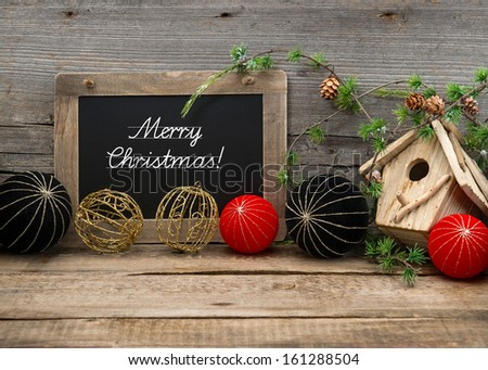 vintage christmas decoration with blackboard for your text over rustic wooden background. red and black china style balls and baubles. sample text Merry Christmas - stock photo