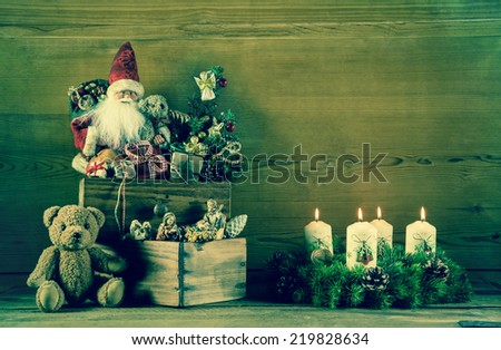 Vintage christmas decoration with santa and advent wreath on wooden background. - stock photo
