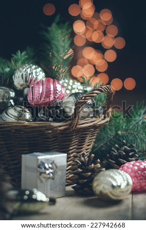 Vintage Christmas decorations in a wicker basket, Christmas gift in retro style, Christmas garlands, cozy home decor. - stock photo