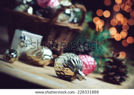 Vintage Christmas decorations in a wicker basket, Christmas gift in retro style, Christmas garlands, cozy home decor, soft focus - stock photo
