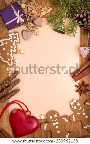 Vintage Christmas decorations on the old paper sheet on wooden background with copy space