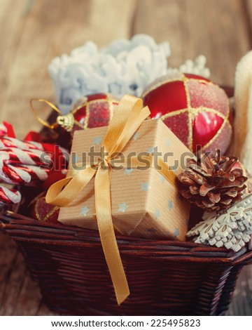 Vintage Christmas Gifts in a Basket,  Sweet Candy toys, Red Balls, Pine cones, Snowflakes. Country style with toned effect