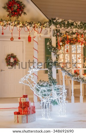 Vintage Christmas house with artificial deer in front of the door and a pile of gift boxes - stock photo