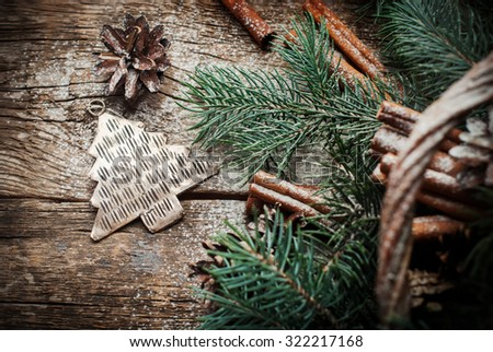 Vintage Christmas Metal Fir Tree Toy, Pine Cones, Cinnamon, Branches of Coniferous on Wooden Table. Rustic Style. Top view - stock photo