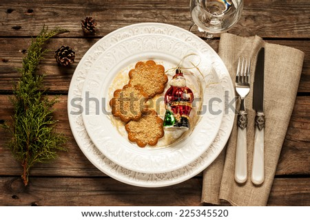 Vintage christmas table setting from above - elegant white plate with ginger cookies, santa claus and natural pine tree branch on rustic planked wood. Country and retro style. - stock photo