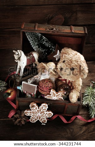 vintage christmas toys like doll,teddy bear,rocking horse and decorations in old treasure chest on wooden background - stock photo