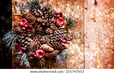 Vintage Christmas wreath with pine cones, sugared apples and red berries hanging on the grungy wooden door. Greeting card. Retro aged photo with scratches.