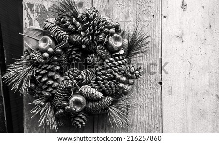 Vintage Christmas wreath with pine cones, sugared apples and red berries hanging on the grungy wooden door. Greeting card. Retro aged photo. Black and white. - stock photo