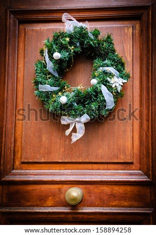 Vintage Christmas wreath with white bows, balls and flower and golden stars on old wooden door. - stock photo
