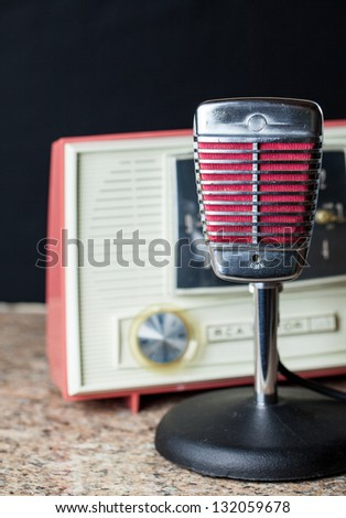Vintage chrome and red microphone with a vintage 50's style radio in the background