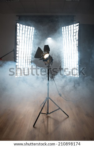 Vintage cinema spot light on trestle standing on wooden floor between two huge projectors enveloped in smoke - stock photo