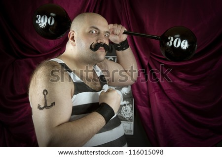 Vintage circus strongman holding big 300 lbs weights. Bald strong man in striped t- shirt lifting heavy weights. Vintage cinema circus scene. Part of larger vintage collection. - stock photo