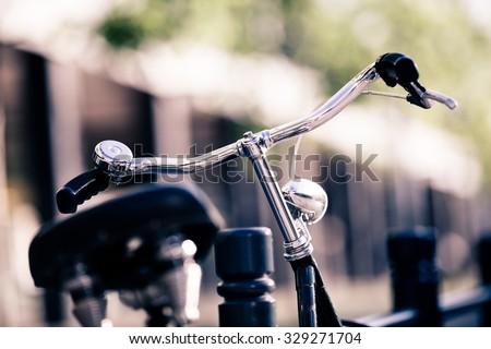 Vintage city bike colorful retro light and handlebar on street, alternative ecology transportation, commute on classic bicycle in urban scene, blurred bokeh background. Selective focus on handlebar. - stock photo