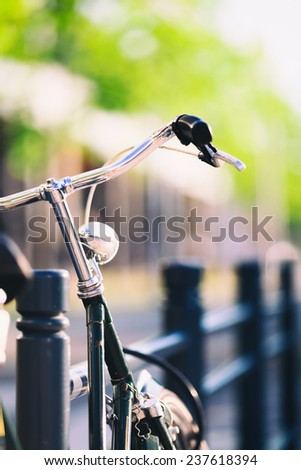 Vintage city bike colorful retro light and handlebar on street, commute on classic bicycle in urban environment, colorful green background