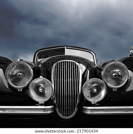 Vintage classic car front view with dark clouds - stock photo